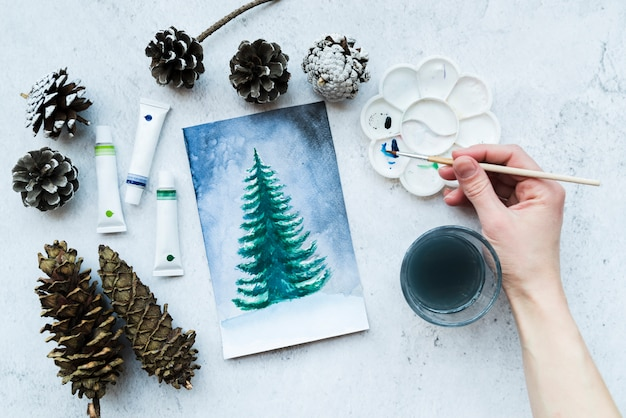 Close-up of a person's hand painting christmas tree with acrylic paint tubes Free Photo