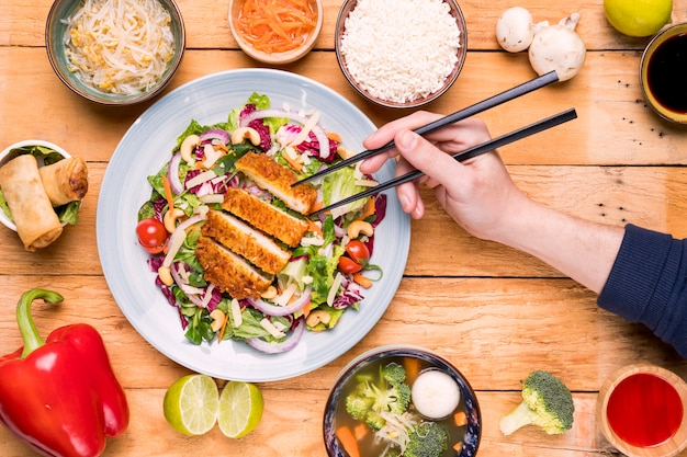 Close-up of a person's hand picking up the fillets with chopsticks on table Free Photo