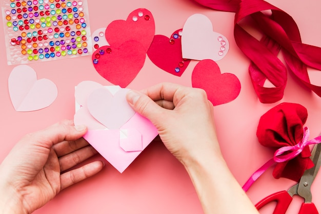 Close-up of a person's hand placing the heart paper inside the pink envelope Free Photo