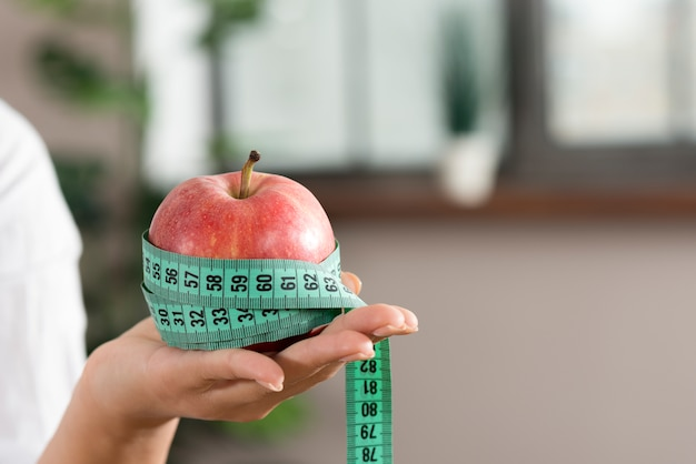 Close-up of person's hand showing red apple with green measurement tape Free Photo