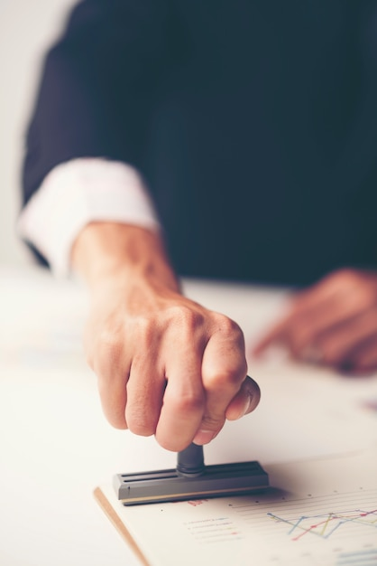 Close-up of a person's hand stamping with approved stamp on document at desk Premium Photo