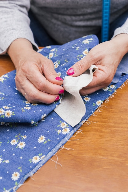 Close-up of a person's hand stitching the floral fabric with