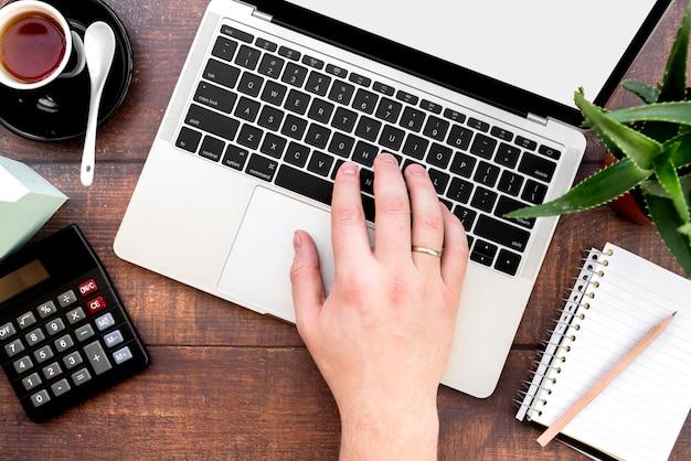 Primo piano della mano di una persona digitando sul computer portatile con calcolatrice; tazza di caffè e blocco note a spirale con la matita sullo scrittorio di legno Foto Gratuite