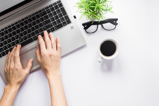 Close-up of a person's hand typing on laptop with coffee cup; eyeglasses and pot plant on white desk Premium Photo