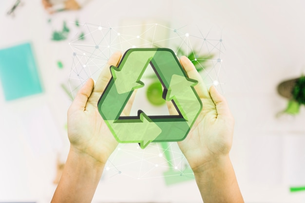 Close-up of a person's hand with recycle icon Free Photo