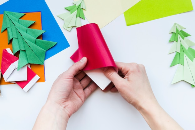 Close-up of a person's making christmas origami on white backdrop Free Photo
