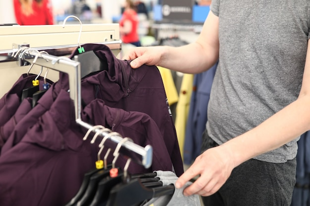Close-up of person in shopping centre. man choosing outerwear in store. stylish and comfy jackets on stamps. adult spending money on clothes. wardrobe change concept Premium Photo