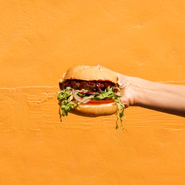 Close-up person with burger and orange background Free Photo