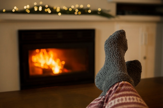 Close-up person with cozy clothes near the fireplace Free Photo