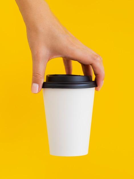 Крупным планом человек с чашкой и желтым фоном Premium Фотографии