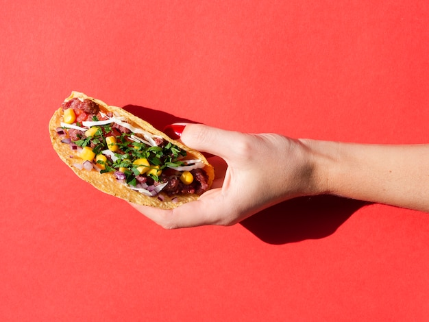 Close-up person with delicious mexican food and red background Free Photo