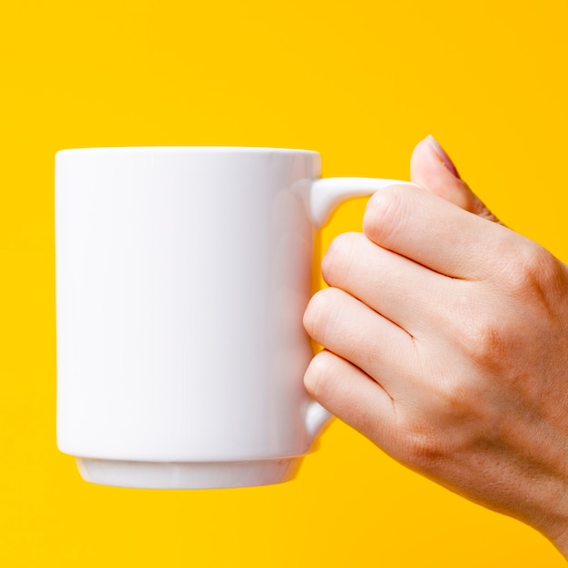 Close-up person with mug and yellow background Free Photo