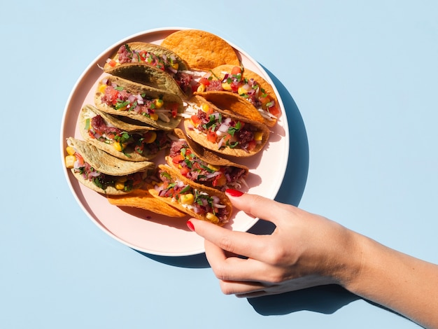 Close-up person with plate full of tacos Free Photo