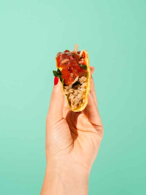 Close-up person with taco and green background Free Photo