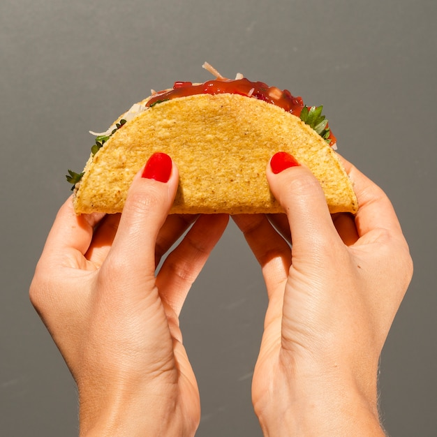 Close-up person with taco and grey background Free Photo