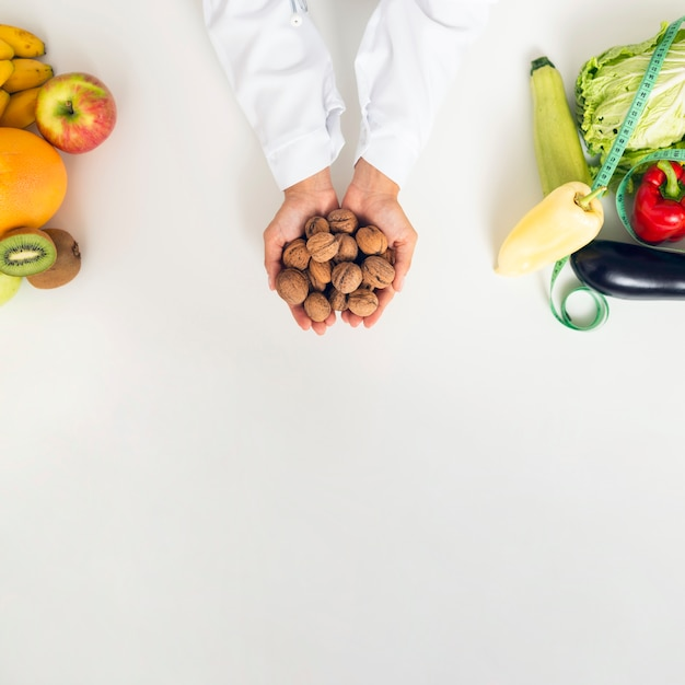 Close-up person with vegetables holding nuts Free Photo
