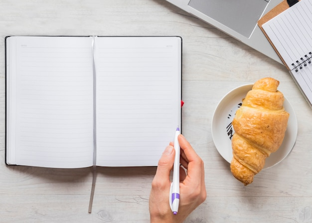 Close-up of a person writing in the diary with pen and croissant on plate over the wooden desk Free Photo