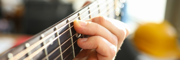 Close-up of persons hand playing on acoustic guitar. macro shot of male performing beautiful melody on musical instrument. hobby for soul. artist and musician concept Premium Photo
