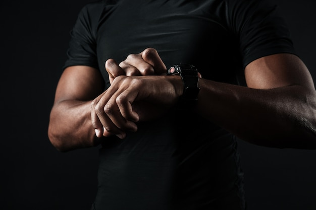Close-up photo of african man in black t-shirt check out time at black wristwatch Free Photo