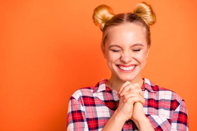 Крупным планом фото привлекательная молодая женщина, одетая в клетчатую рубашку, изолированную на оранжевом Premium Фотографии