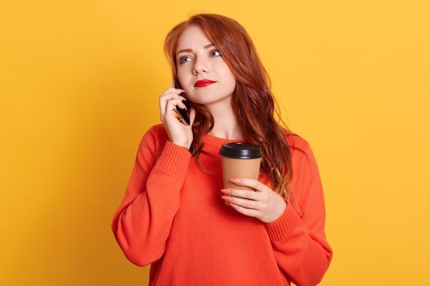 Close up foto bella signora aperta, tenendo la bevanda calda in un contenitore di carta isolato, parlando al telefono Foto Gratuite