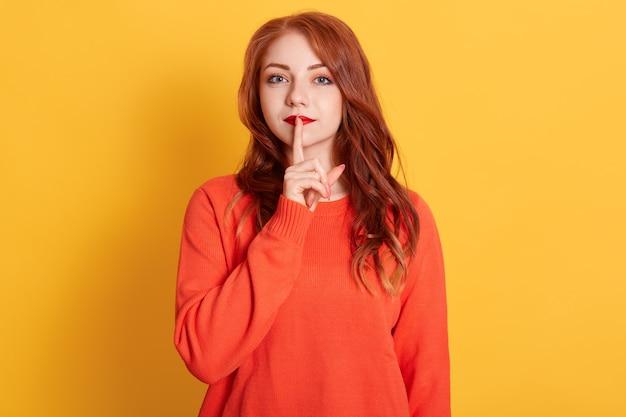 赤いポマード、長い赤い髪型、人差し指を口の近くに保ち、写真の美しい女性を閉じます 無料写真