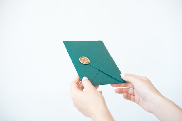Close-up photo of female hands holding a green invitation envelope with a wax seal, a gift certificate, a postcard, a wedding invitation card. Premium Photo