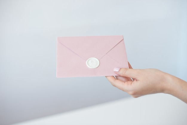 Close-up photo of female hands holding invitation envelope with a wax seal, gift certificate, postcard, wedding invitation card Premium Photo