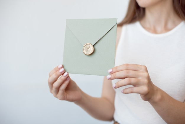 Close-up photo of female hands holding invitation envelope with a wax seal, gift certificate, postcard, wedding invitation card. Premium Photo