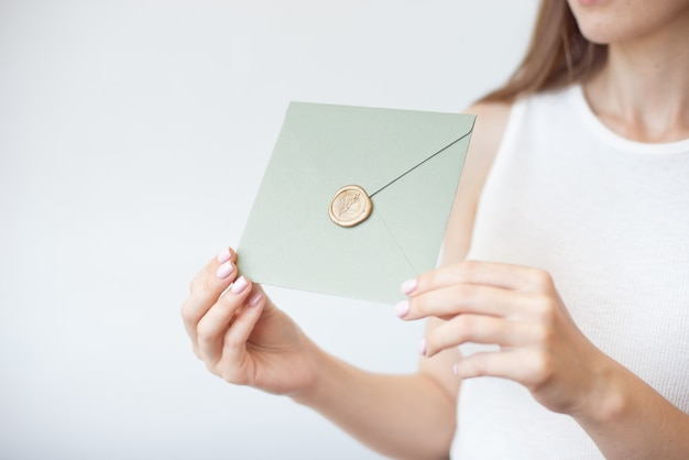 Close-up photo of female hands holding a silver blue or pink invitation envelope with a wax seal, a gift certificate, a postcard, a wedding invitation card. Premium Photo