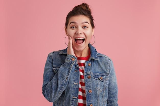 Primo piano foto di donna con le lentiggini, vuole raccontarvi la notizia scioccante, mette una mano in faccia, indossa una t-shirt a righe giacca di jeans, guardando la telecamera, isolata su un muro rosa. Foto Gratuite