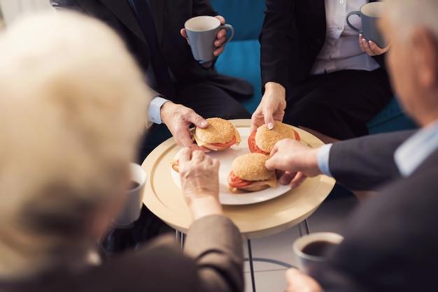 Close-up photo of four hamburgers on a plate and four hands. Premium Photo