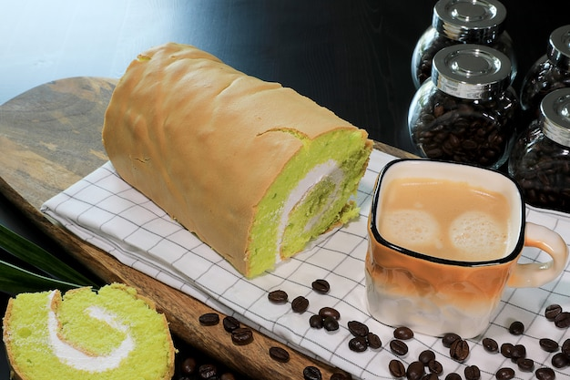 Close-up photo fresh hot coffee in the brown and white color cup with coffee beans, and pandanus yam roll cake with white cream inside. Premium Photo