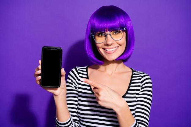Close up photo of lovely youth holding device advertising wearing eyewear eyeglasses striped shirt isolated over purple violet background Premium Photo