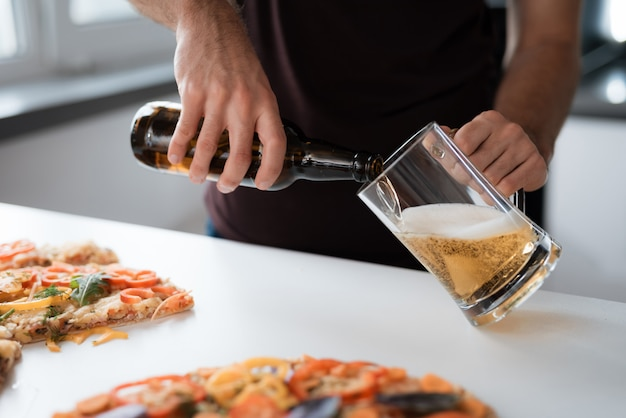 Close-up photo of a man pours beer into a glass. Premium Photo