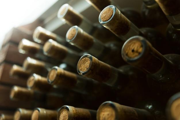 Close up photo of many bottles of wine laying  underground,  wine concept Premium Photo