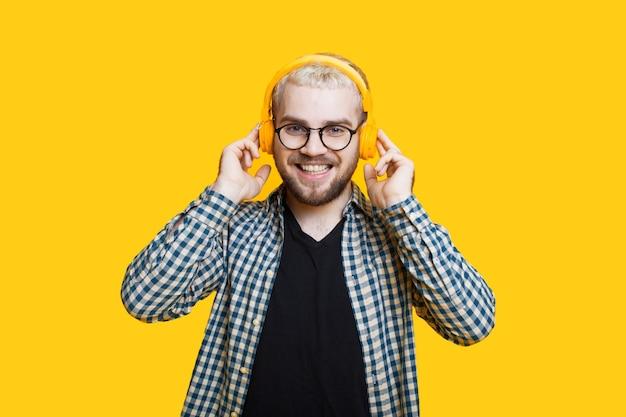 Крупным планом фото бородатого кавказца со светлыми волосами в наушниках и очках, позирующего на желтой стене Premium Фотографии