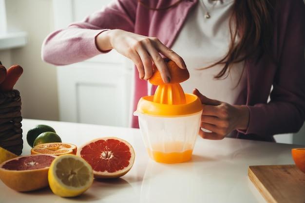 Крупным планом фото апельсинового сока, выжатого соковыжималкой кавказской женщиной со здоровыми привычками Premium Фотографии