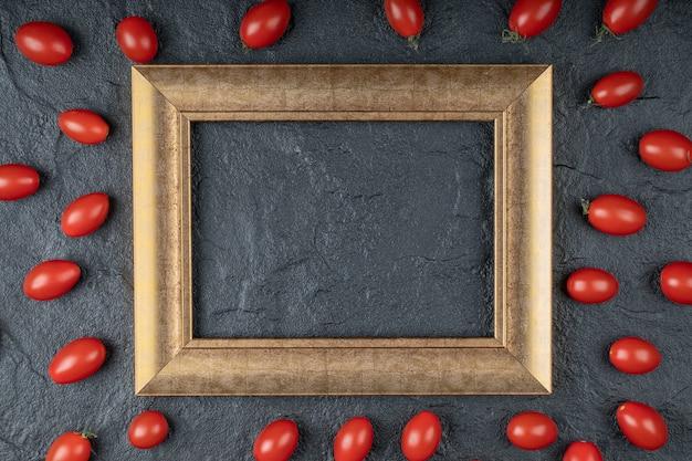 Закройте фото помидоров черри вокруг золотой рамки на черном фоне. фото высокого качества Бесплатные Фотографии
