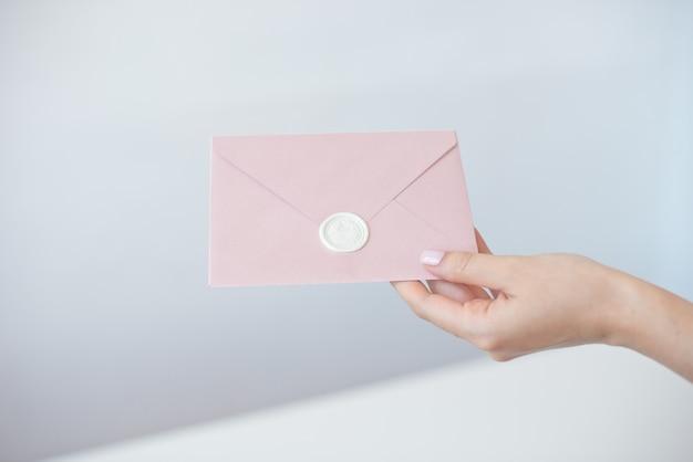 Фото конца-вверх женских рук держа конверт приглашения с сургучной печатью, подарочный купон, открытку, карточку приглашения свадьбы. Premium Фотографии