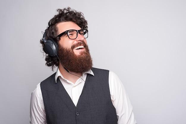 ヘッドフォンを着用し、音楽を聴く青年実業家の写真をクローズアップ。ゆったりとした時間。 Premium写真