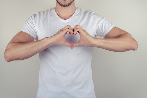 회색 회색 벽 복사 공간에 고립 된 가슴에 마음을 만드는 잘 생긴 귀여운 좋은 매력적인 근육 질의 남자의 사진 초상화를 닫습니다 프리미엄 사진