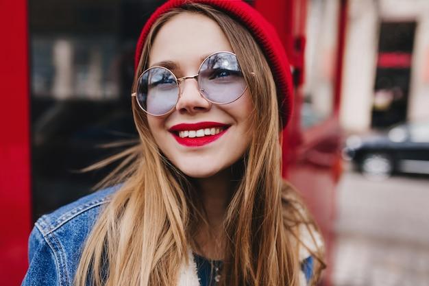 Foto del primo piano della romantica ragazza bianca indossa occhiali rotondi che osserva in su con il sorriso. giovane signora vaga con trucco luminoso che posa accanto al bus rosso. Foto Gratuite
