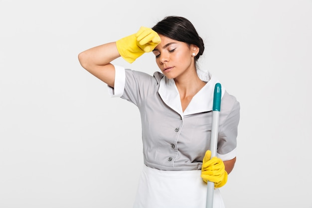 Close-up photo of tired brunette girl in uniform holding mop and wipes sweat from her forehead Free Photo