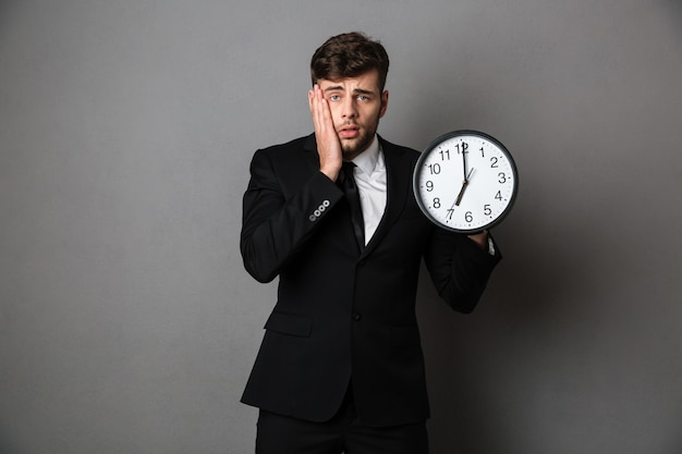 Close-up photo of upset worker in suit holding clock, Free Photo
