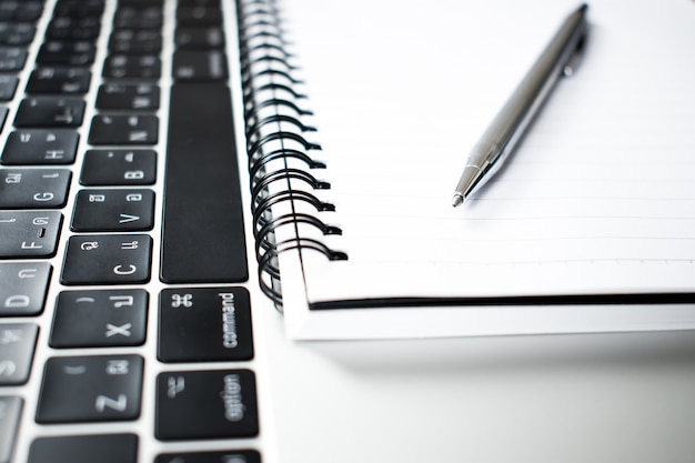 A close up photograph of a pen placed in a notebook and a computer of a young businessman. Premium Photo