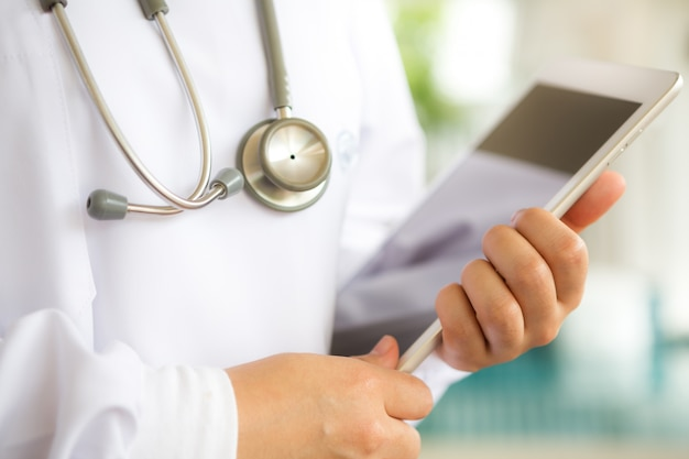 Close-up of physician holding a tablet Free Photo