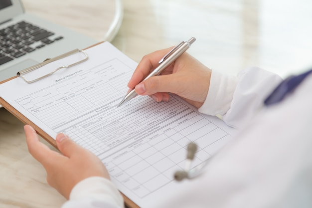 Close-up of physician's hands with clipboard and pen Free Photo