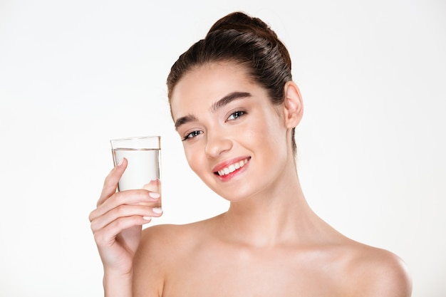 Close up picture of glad gorgeous woman being half-naked drinking minaral water from transparent glass with smile Free Photo