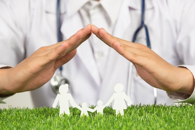 Крупным планом изображение рук доктора, размещающее символ дома над моделью члена семьи Бесплатные Фотографии